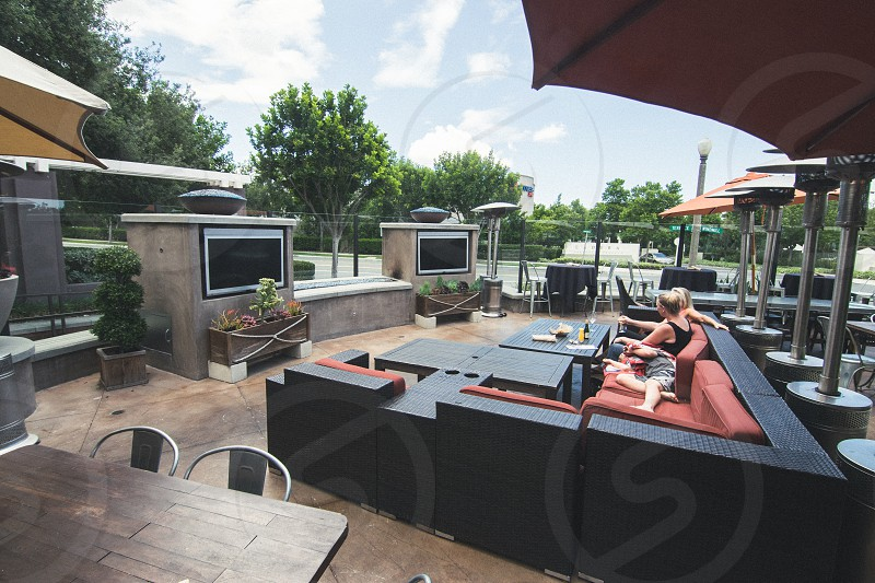 black wooden base red fabric padded sectional couch on lobby with black rectangular patio table with drinks and food table and woman and man sitting on couch with green trees on view photo