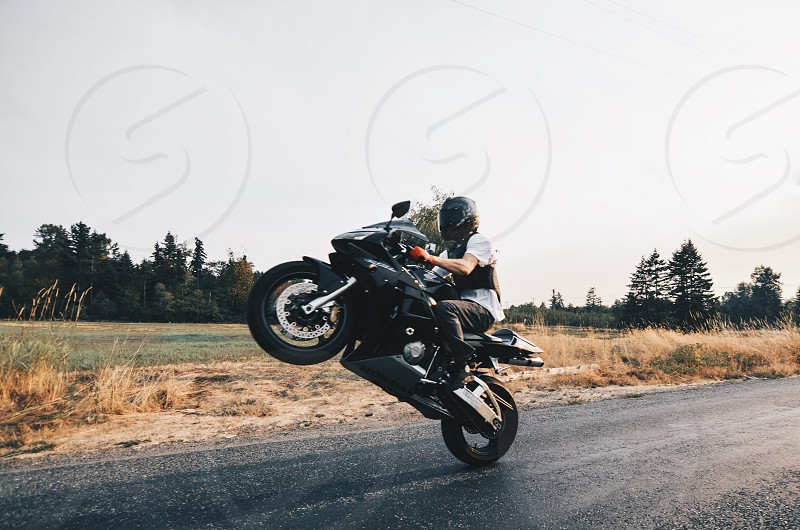 person in white t shirt doing a stunt on black superbike by the asphalt road during daytime photo