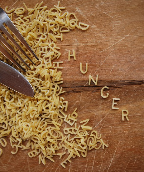 Hunger spelt out in alphabet pasta shapes on chopping board with knife and fork photo