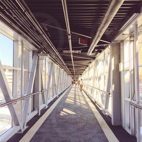hallway between railings during daytime photo