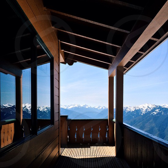 empty brown wooden terrace with view of snow capped mountain range during daytime photo