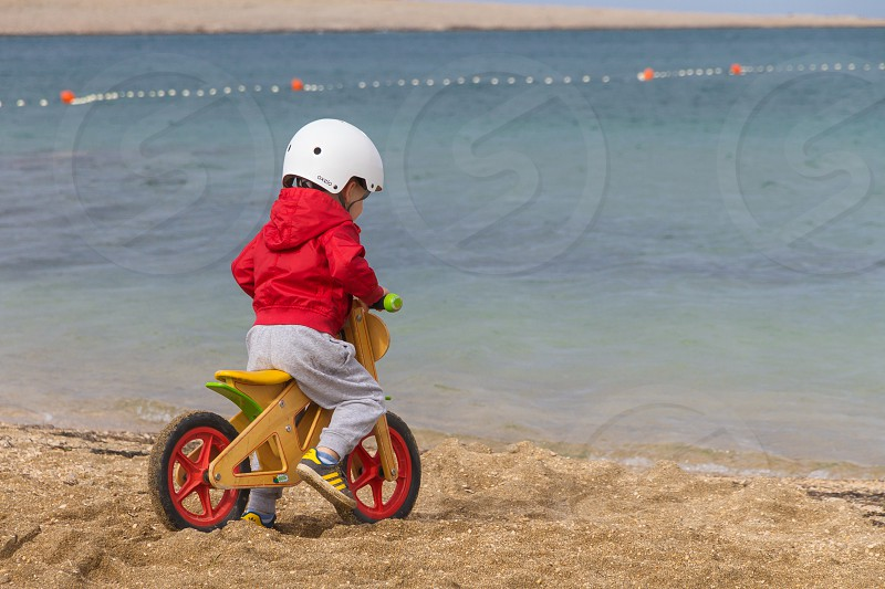 boy in red jacket driving bike on the beach and looking in sea photo