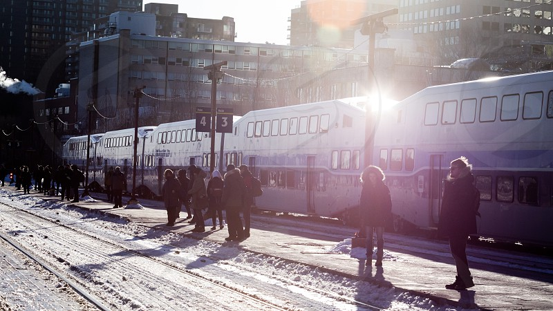 People waiting for the train to commute back home under a frigid winter sun in Montreal Canada.  photo