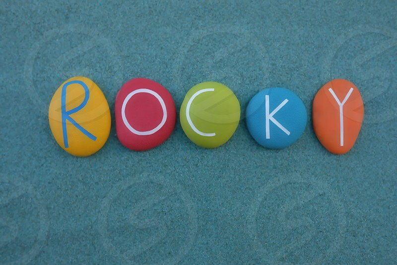 Rocky male given name composed with multi colored stone letters over green sand photo