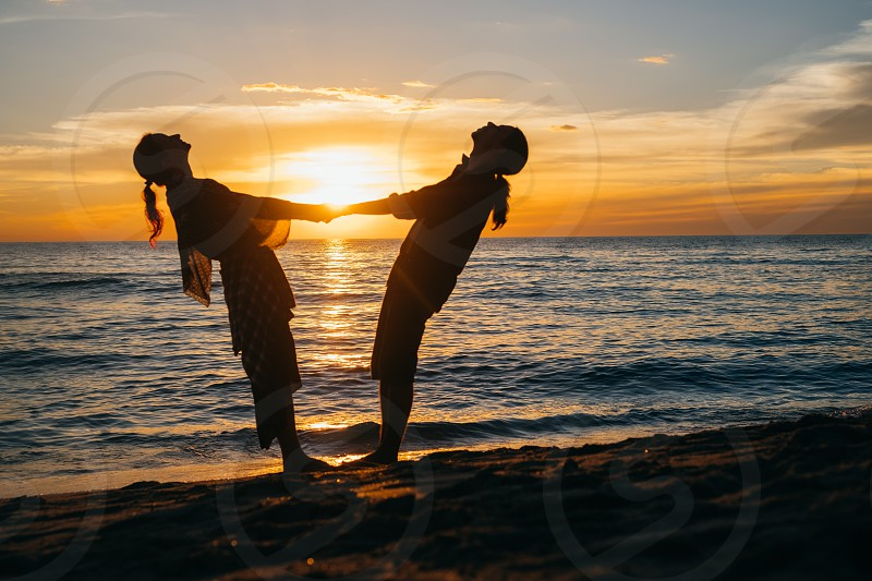 Young couple is performing a move of pleasure during dusk or dawn at the beach photo