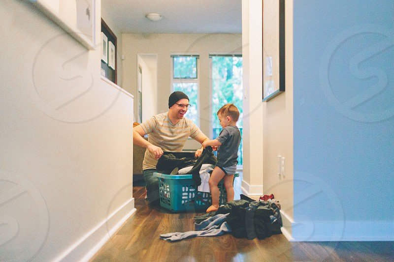 A father and his son doing laundry at home. photo
