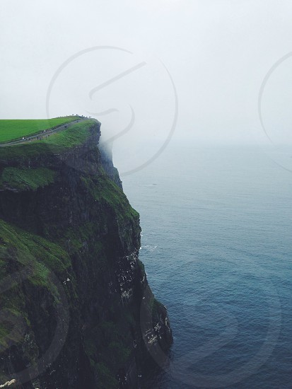 people walking on road between green grass towards cliff edge with blue sea underneath during foggy weather photo