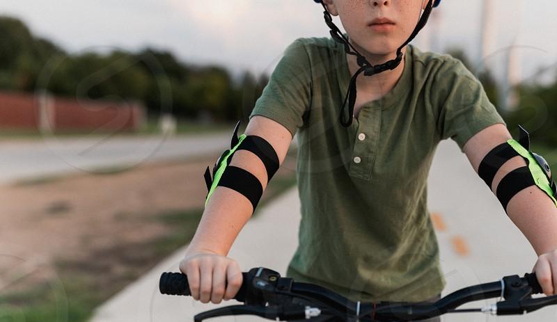 A boy rides a bicycle.  photo