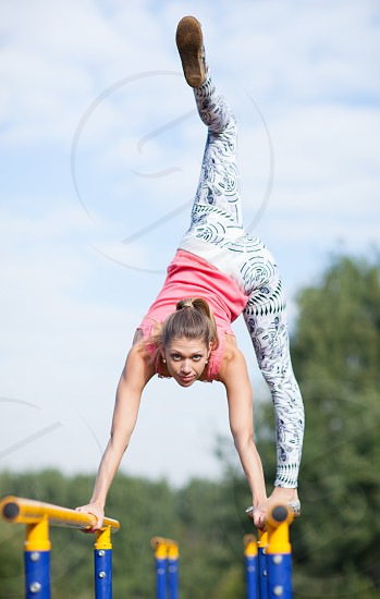 Agile attractive young female gymnast balancing on brightly coloured cross bars outdoors in a park with her leg raised high in the air photo