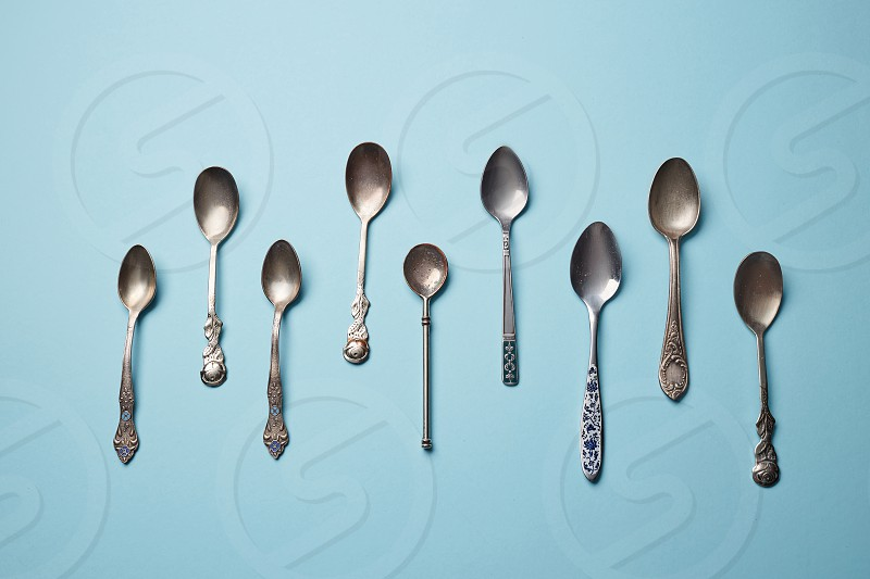 Collection of different vintage metal spoons on a blue paper background top view photo
