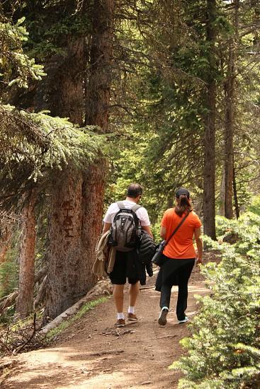 man and woman walking down a hiking trail photo