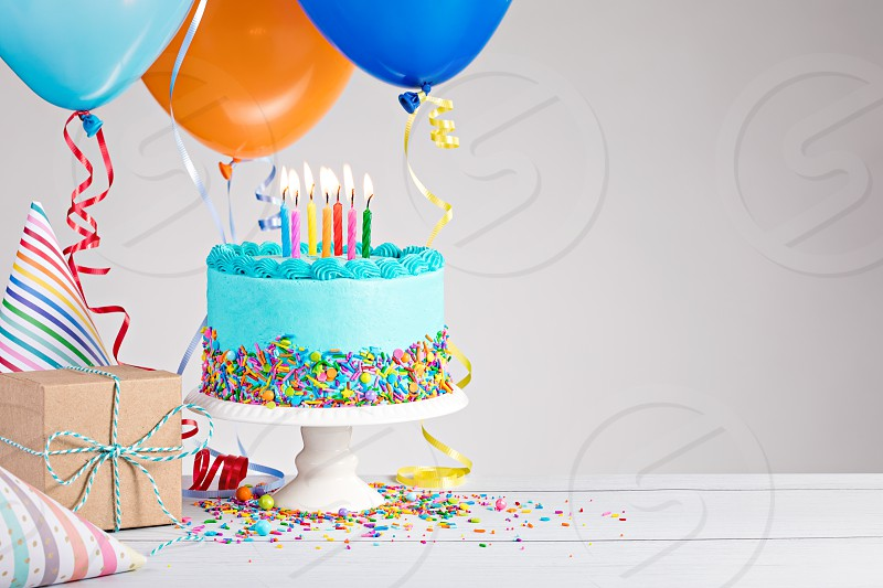 Blue Birthday cake presents hats and colorful balloons over light grey. photo