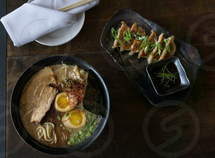sliced boiled egg meat and noodle soup on black ceramic round plate near sliced meat with green vegetable toppings and sauce placed on brown wooden table photo