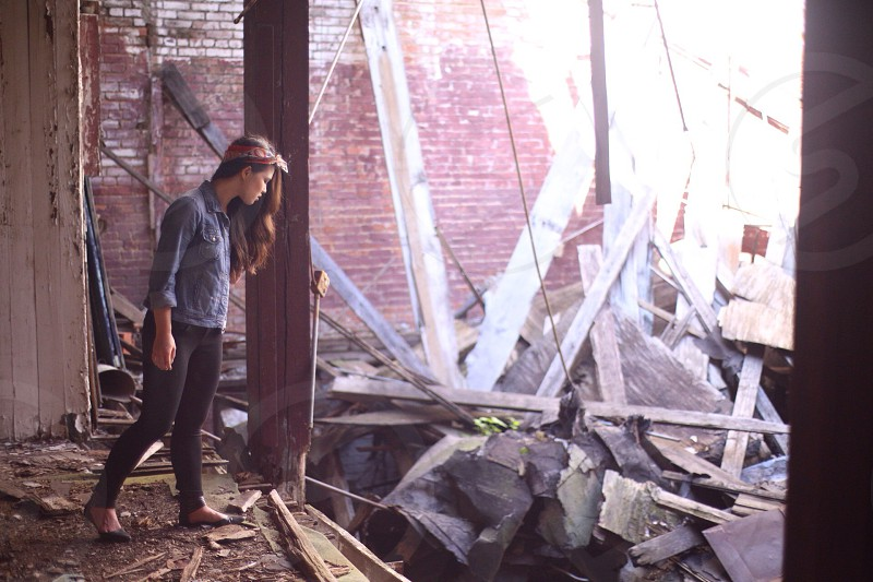 Girl wearing a denim shirt looking at the rubble photo