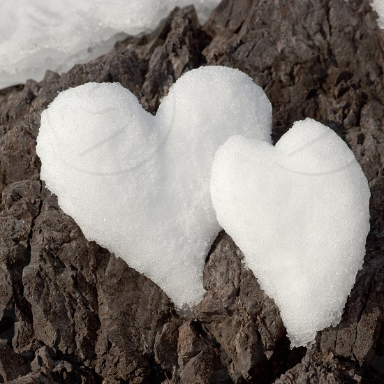 Two Valentine's Day Hearts of love formed from snow on rock surface photo