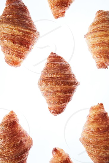 Tasty fresh french croissants pattern on a white background. Continental breakfast concept. Copy space. Close up. photo