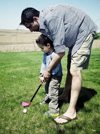 man in button down shirt teaching boy how to play golf photo