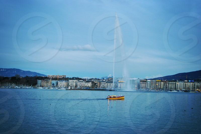orange boat sailing near white concrete buildings at daytime photo