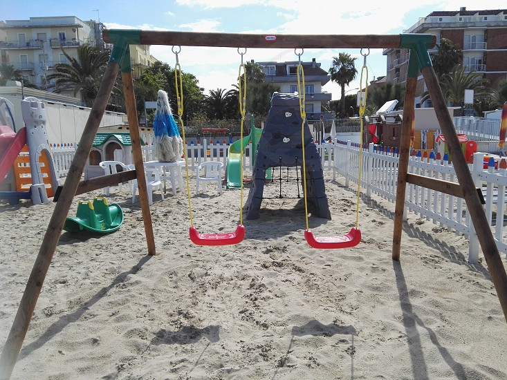 playground in the sand with swings surrounded by a white fence photo