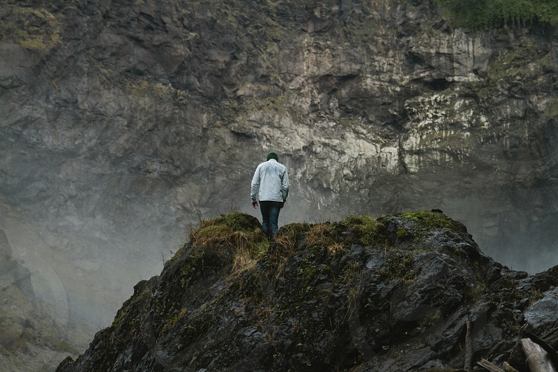 man standing on rock formation photo