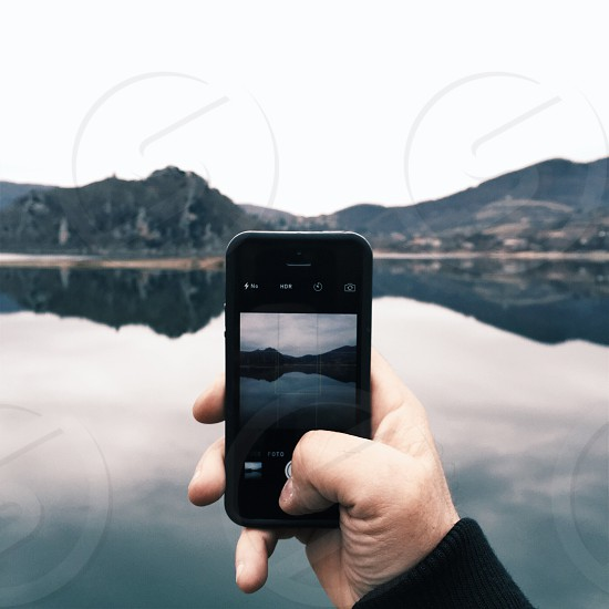 """""""Trough my iPhone"""" - man using iPhone camera taking a picture of a lake photo"""