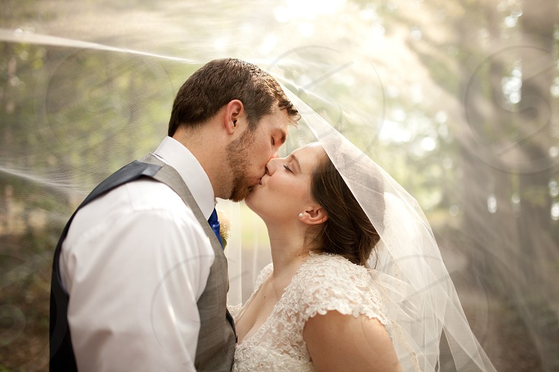 newlywed couple kissing under woman's white lace cape photo