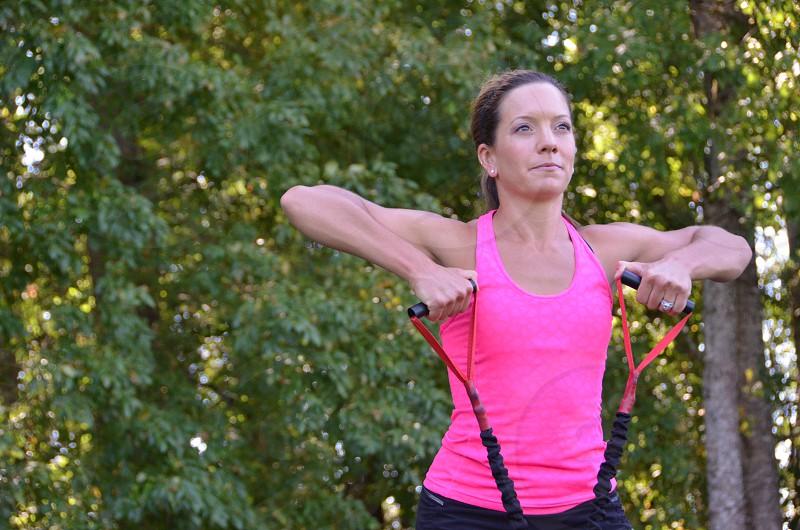 Female trainer exercise band upright rows photo