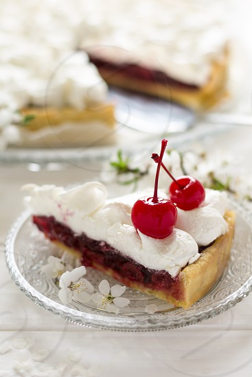 Slice of homemade pie with cherry and meringue decorated cherry blossom on white wooden desk photo