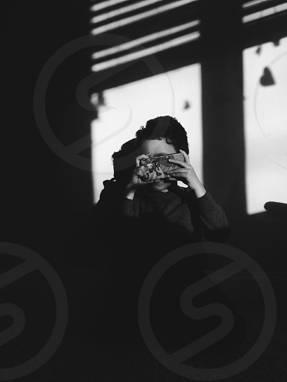 child covering his face with smartphone grayscale photography photo