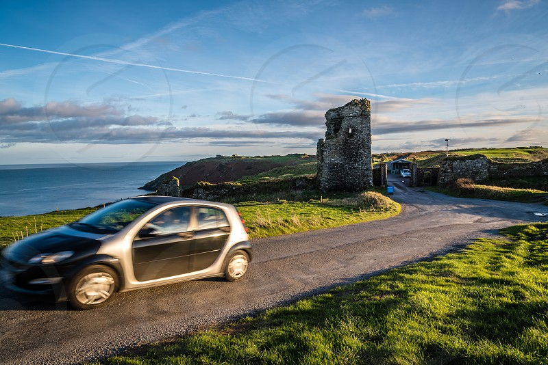 Scenic view of car moving on beautiful coast road  at sunset. Kinsale Ireland photo