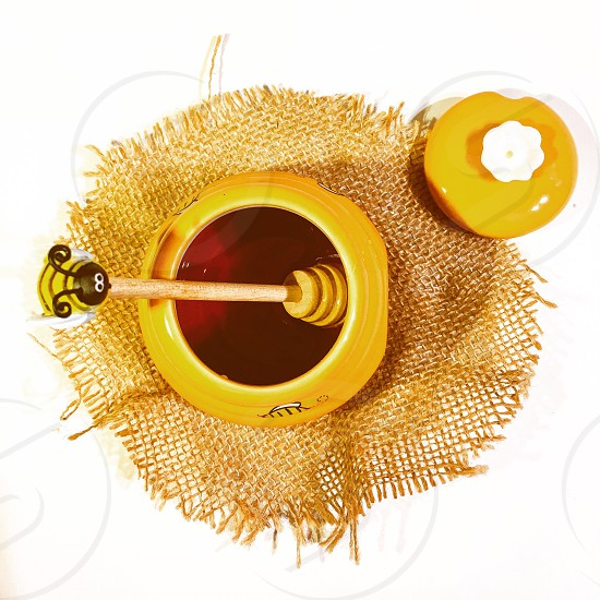 a yellow canister with bee end honey dipper placed on top of brown round strainer with the canister cap on the edge photo