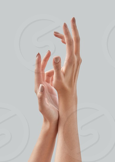Close up image of beautiful woman's hands with light manicure on the nails on a gray background. Skin care for hands manicure and beauty treatment. Place for text. photo