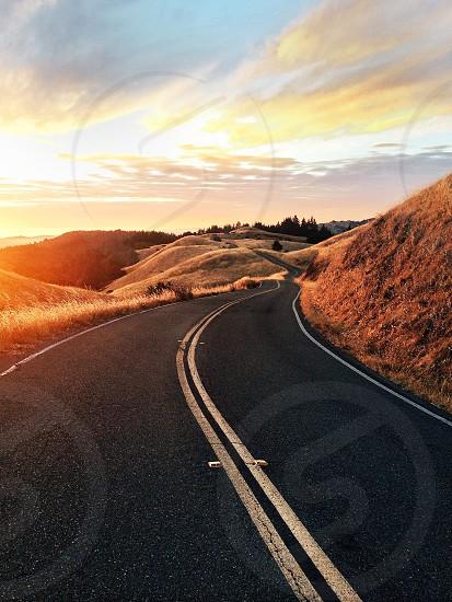 sunrise over open road through hills photo