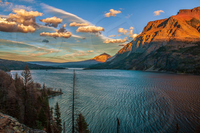 Beautiful red mountains over St Mary lake at sunset photo