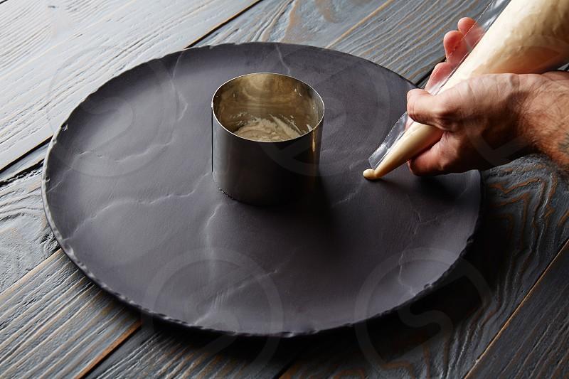 pannacotta preparation with chef hands on black slate dish photo