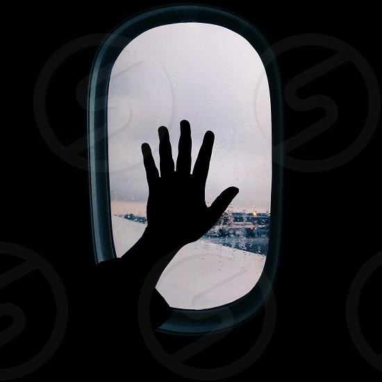 hand on plane window photo