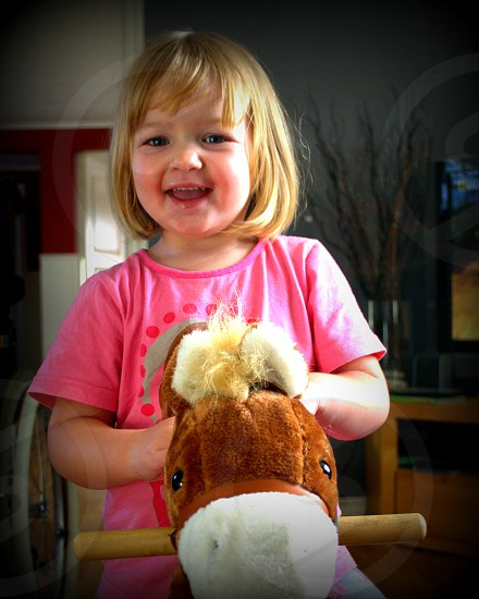 girl wearing pink t shirt smiling and riding a horse rocker photo