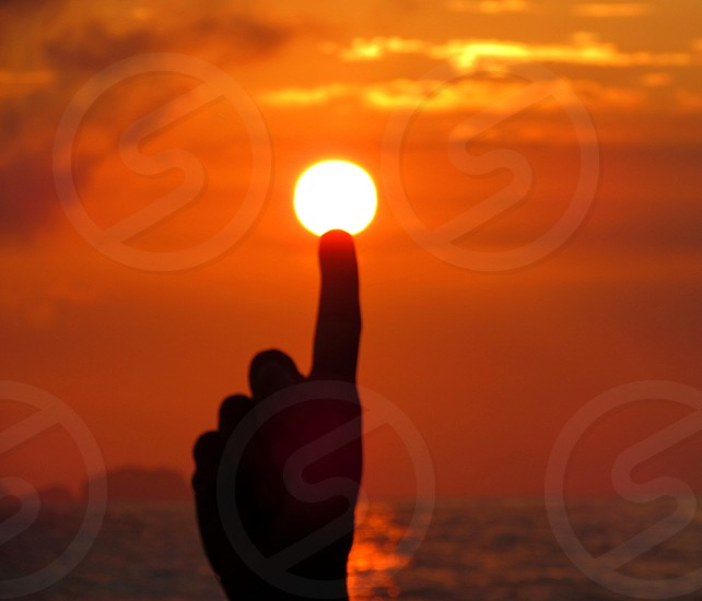 silhouette of finger touching the orange sun during twilight photo