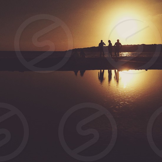 3 people standing near the water photo