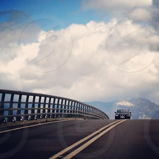 black car approaching on bridge photo