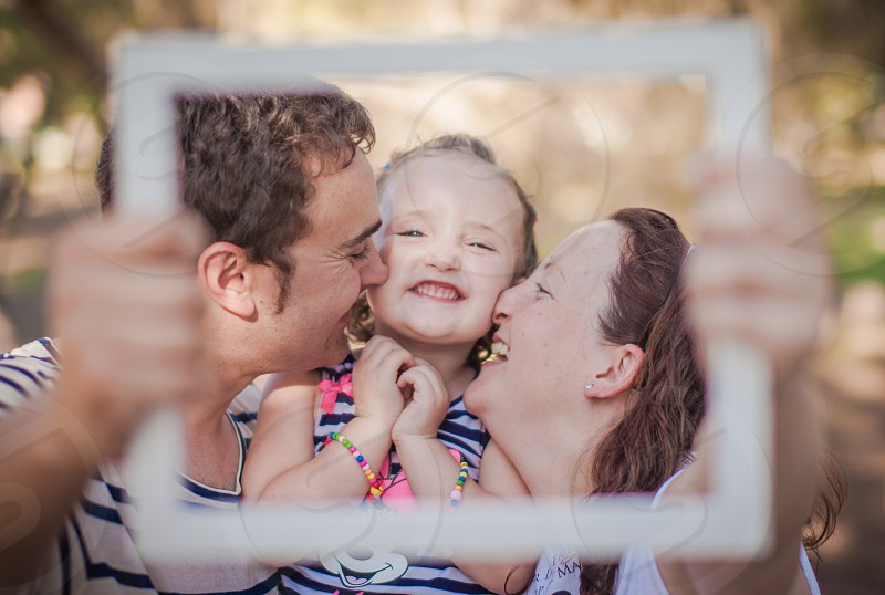 man and woman kissing girls cheeks while holding white photo frame during daytime photo