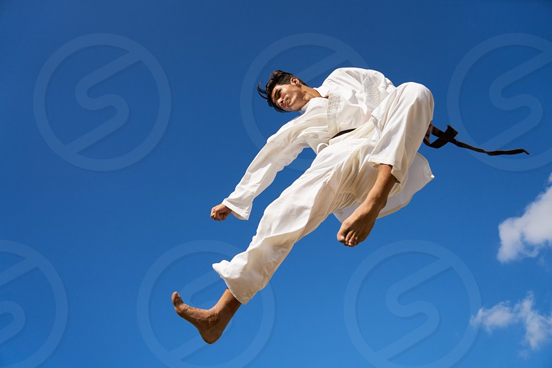 Young people athlete sport activity combat and extreme sports. Hispanic man exercising in karate and traditional martial arts jumping mid-air in the sky photo