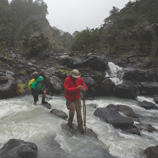 Two hikers crossing a river photo