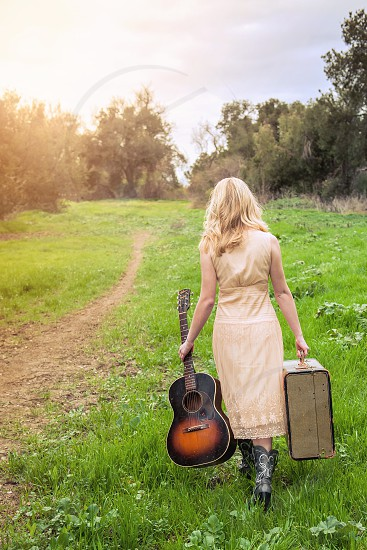 Young Blonde Woman walking in field carrying old suitcase and guitar and wearing cowboy boots. photo