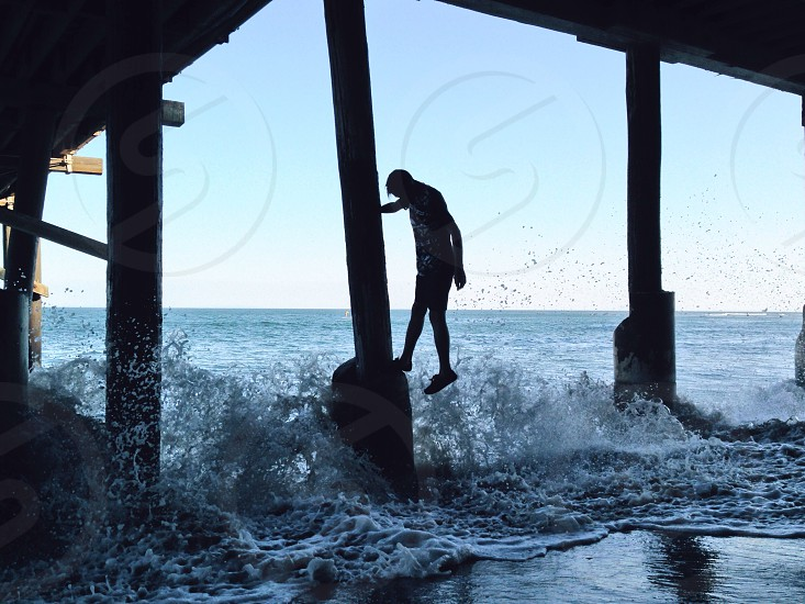 man on pier pedestal as wave crashes photo