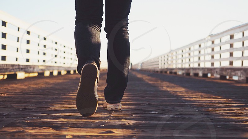 person wearing black pants walking on wooden pier  photo