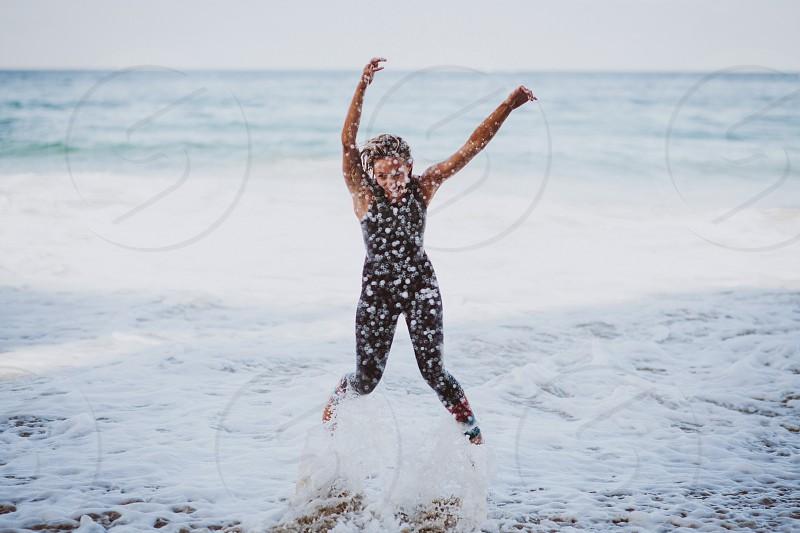 woman in black rash guard jumping on seaside during daytime photo