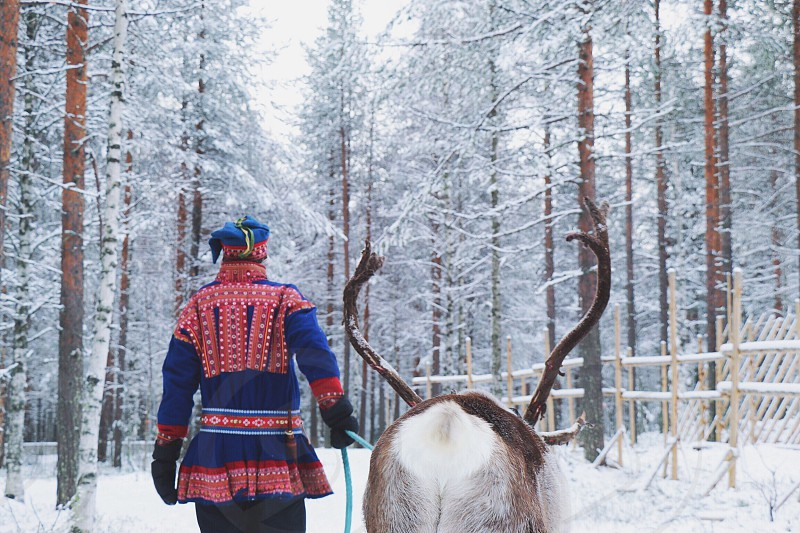 man in red and blue suit holding brown and white deer walking on snow during daytime photo