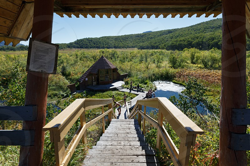 NALYCHEVO NATURE PARK KAMCHATKA PENINSULA RUSSIA - SEP 7 2013: Wooden staircase leading to the hot springs thermal pools with healing mineral water facilities for swimming outdoors tourists and travelers with a wooden dressing room. photo