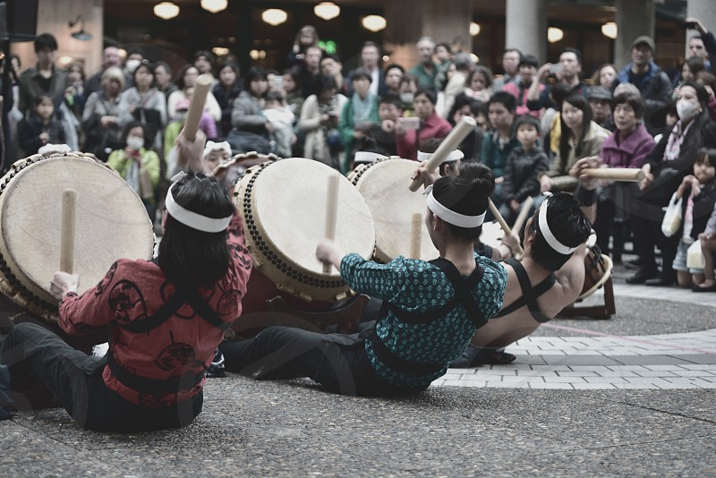 3 people sitting on concrete ground while playing drums near crowd watching during daytime photo